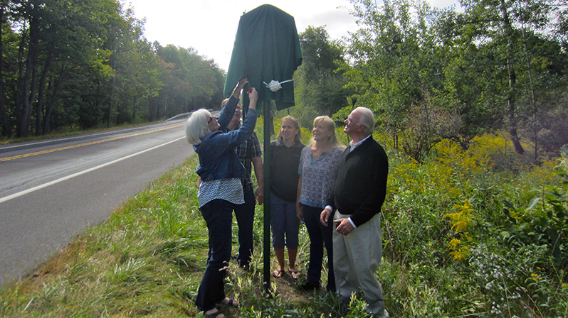 Susan Blakeslee Borden unveils the historical marker for ancestor Jacob Blakeslee Jr., as (from left) William Blakeslee, Wendy Blakeslee White, Amy Blakeslee Henry and Jerome Blakeslee look on.