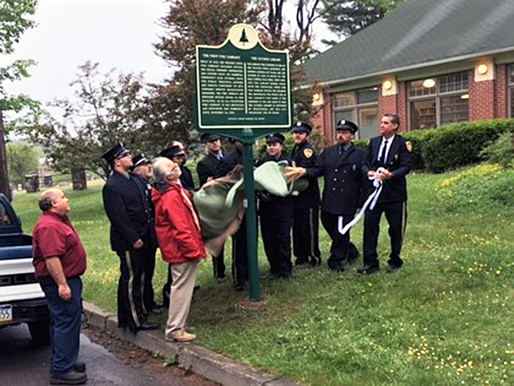 Fire company members unveil the marker, located outside the Clymer Library.