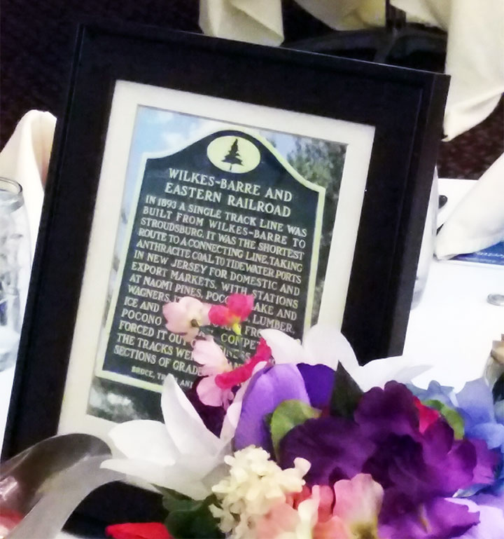A photograph of the historical marker for the Wilkes-Barre and Eastern Railroad graces a table with the centerpiece.