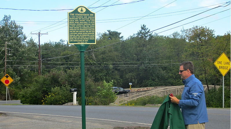 Robert Jones, general manager of the Lake Naomi Club, unveils the Stagecoach Inn historical marker.