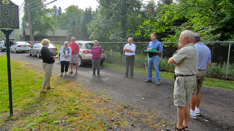 Trudi Denlinger, left, addresses those gathered for the dedication of the Wagner's Tree Farm historical marker.